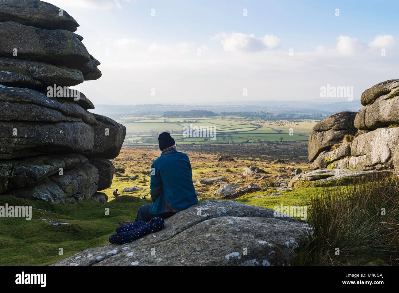 A man comtemplates the view of Dartmoor and beyond from his seat atop Pew Tor, Dartmoor National Park. Stock Photo