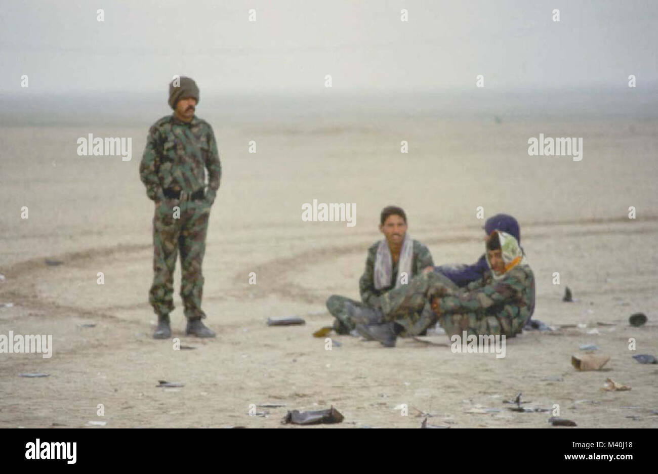Iraqi soldiers sit along-side a dirt road waiting to surrender to U.S. Forces during Operation Desert Storm. Iraq - Stock Image