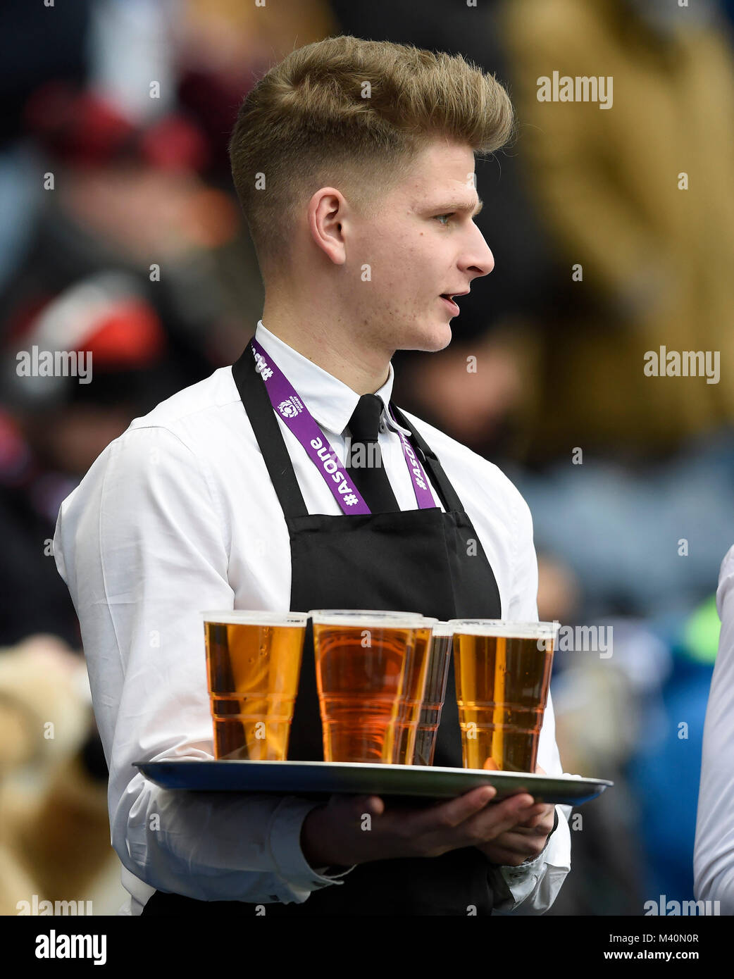 A waiter holding a tray of beer before a Six nations rugby international at BT Murrayfield Stadium, Edinburgh. - Stock Image