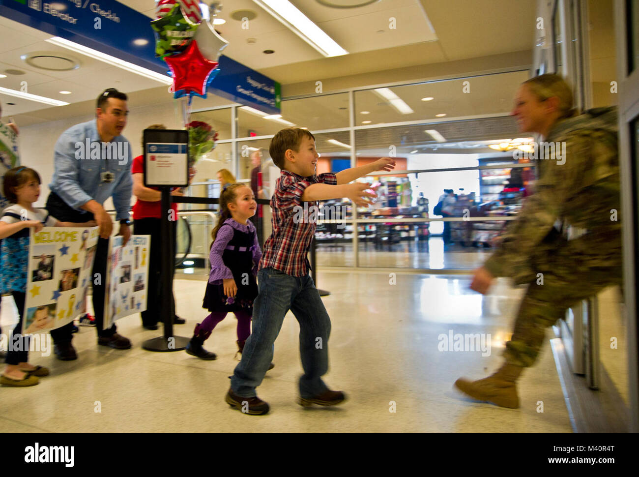 Eva Gamez, 4, and her brother, Tomas, 6, rush to meet their mother, Tech. Sgt. Christina Gamez, as she returns to - Stock Image
