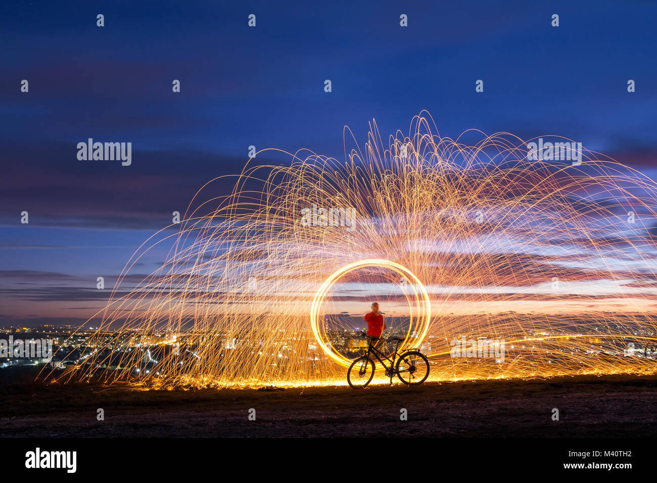 Firework showers of hot glowing sparks from spinning steel wool over night city background. Art show of spinning Stock Photo