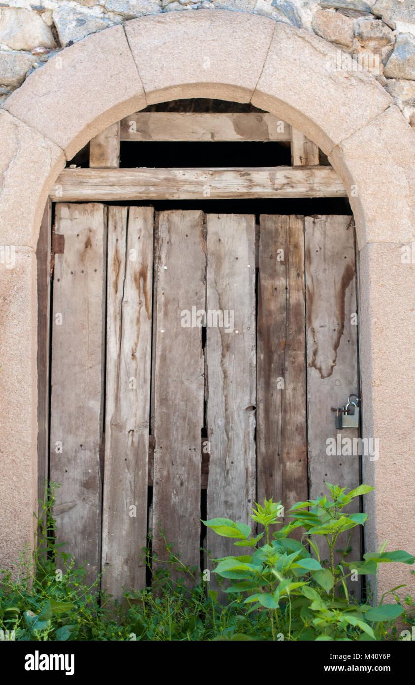 Ancient wooden door in stone wall Stock Photo