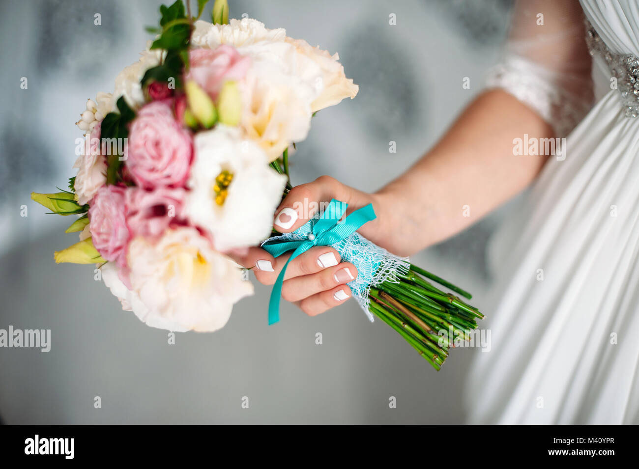 Bride holding wedding bouquet in your hand white and pink flowers bride holding wedding bouquet in your hand white and pink flowers with blue ribbon brides manicure with a heart close up mightylinksfo