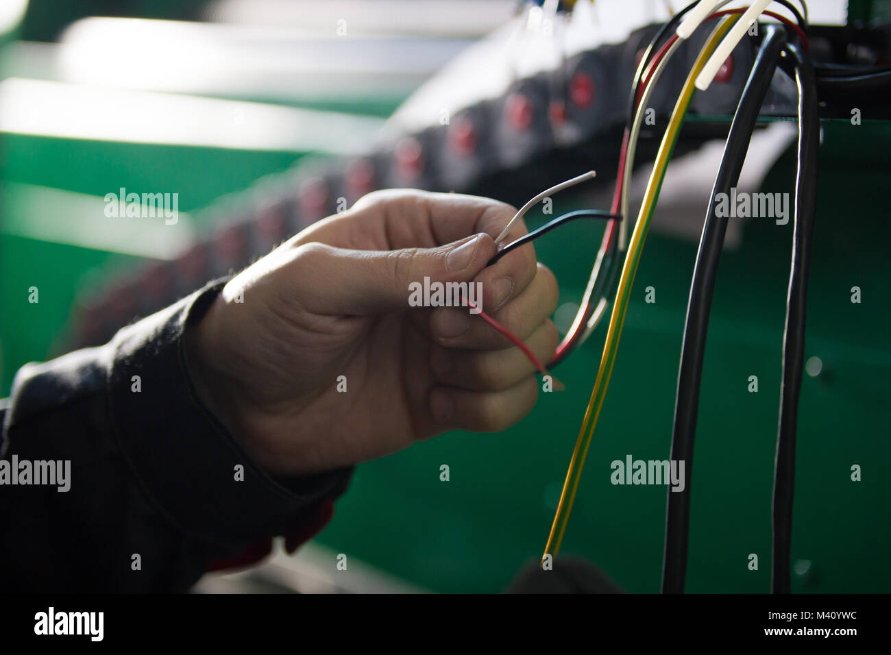 Electrician works with hands of electric - Stock Image