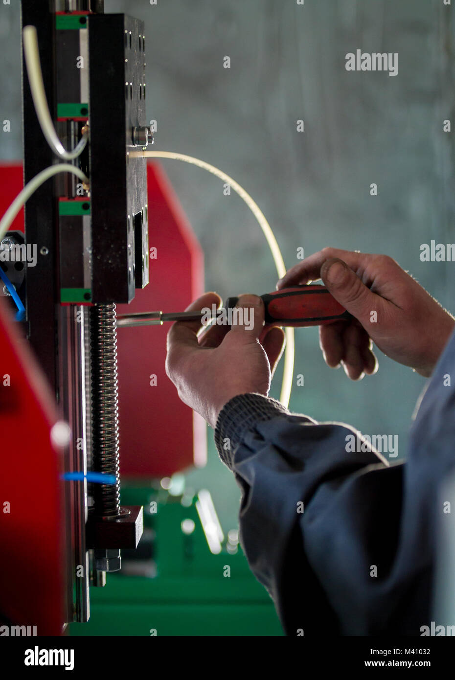 Hands of worker with screwdriver - repairs of machinery equipment - Stock Image