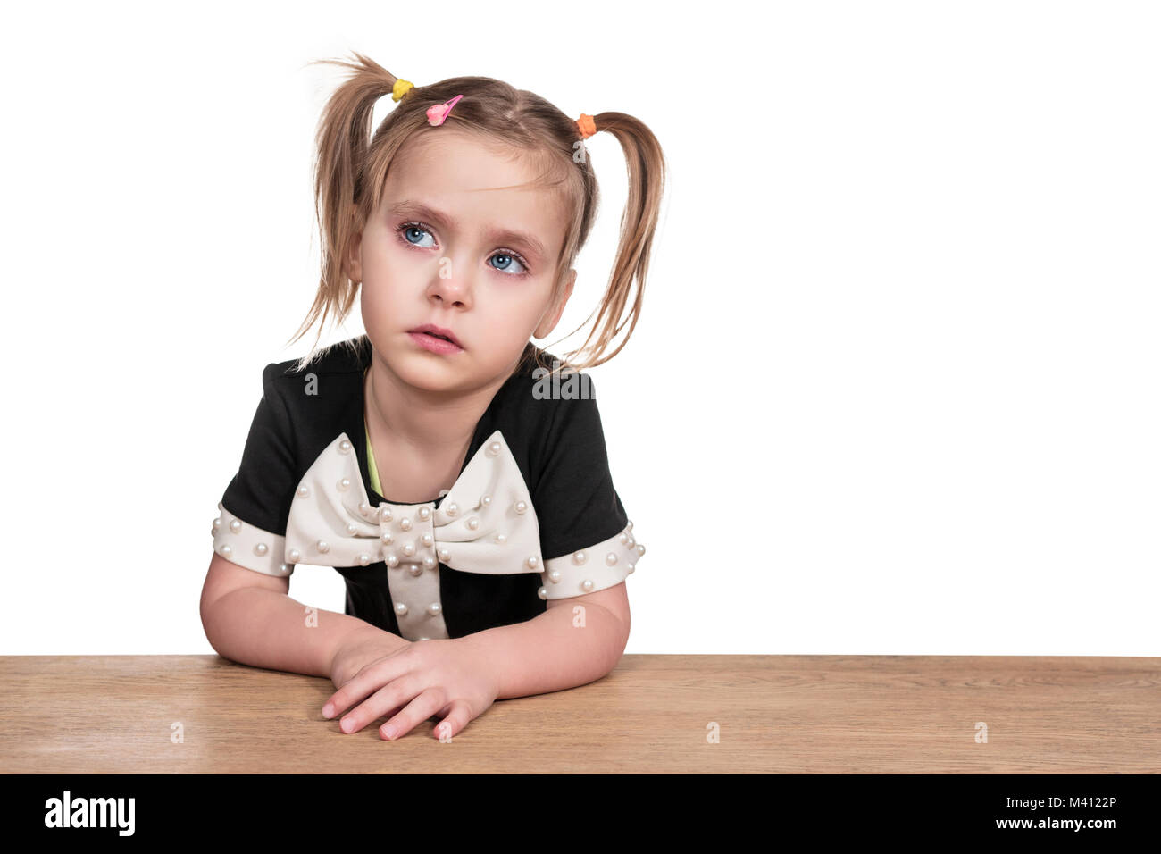 Little beautiful upset girl with tearful eyes sitting at table isolated on white background - Stock Image