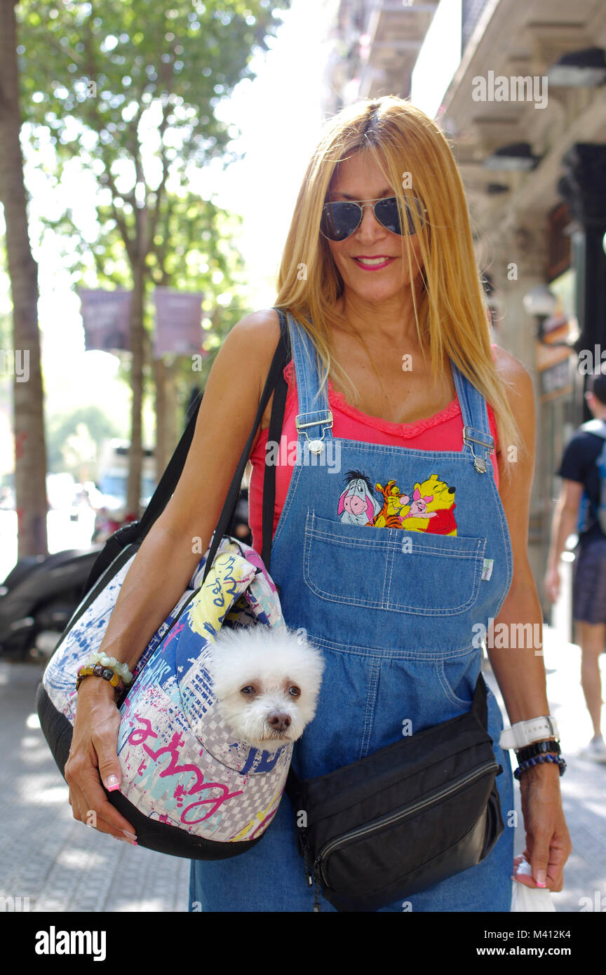Blonde woman in Barcelona carrying a Maltese dog in a shoulder bag - Stock Image