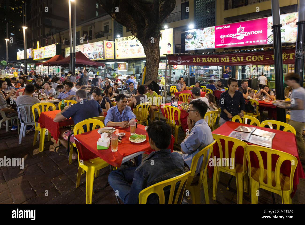 Kuala Lumpur, Malaysia - December 22 2017: Tourists and locals eating in Jalan Alor famous for its chinese food - Stock Image