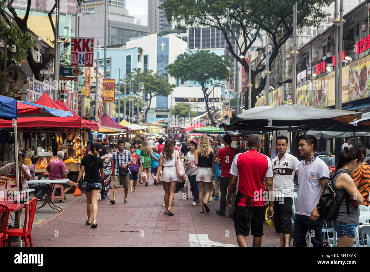 Kuala Lumpur, Malaysia - December 22 2017: Tourists and locals wander along Jalan Alor famous for its chinese food - Stock Image