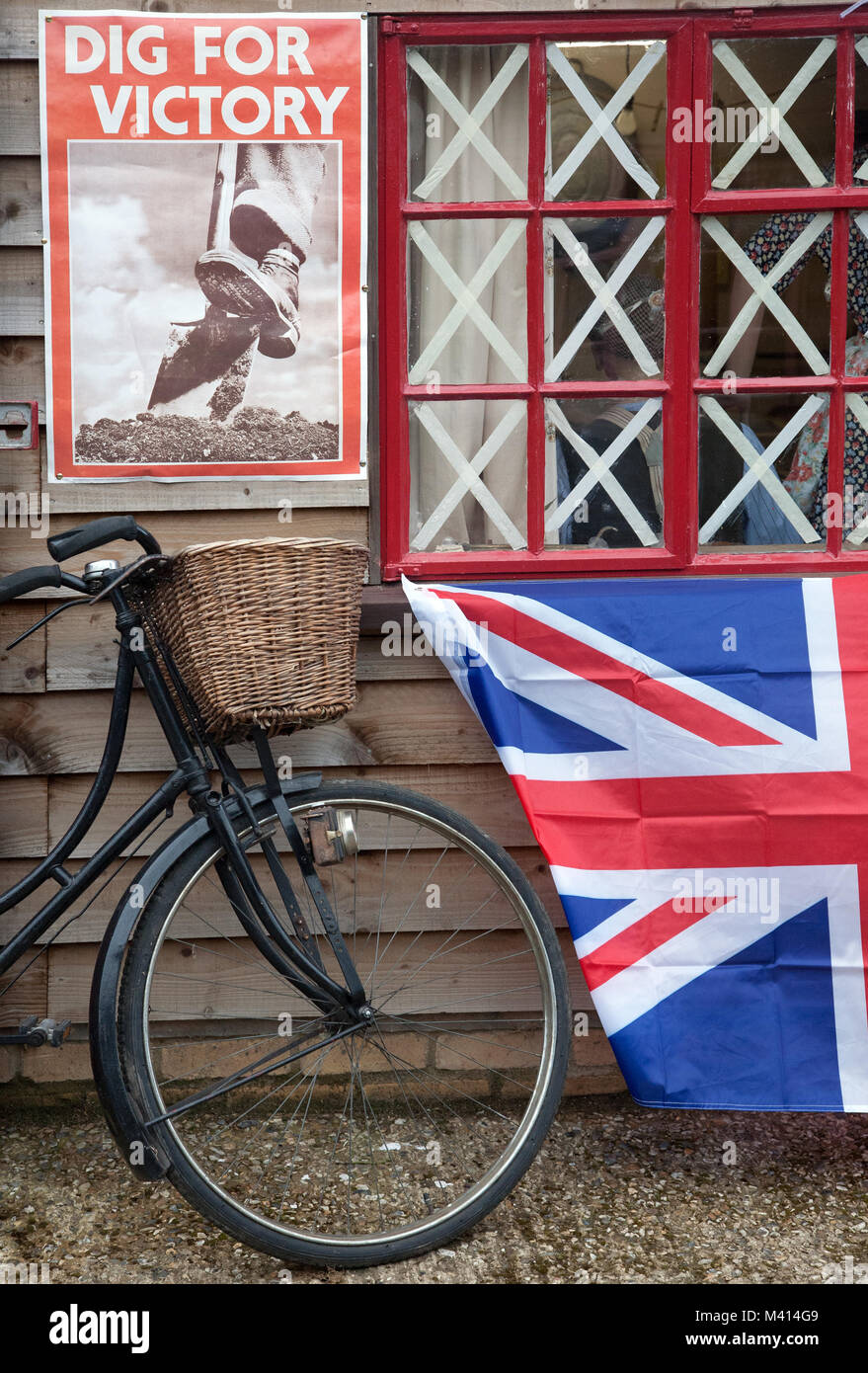 An old bicycle, a Union flag and a World War 2 'Dig For Victory' poster outside a wooden hut at Pitstone - Stock Image