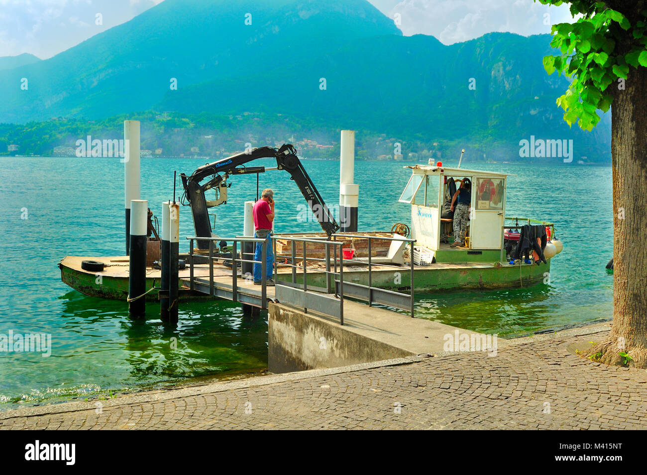 Freight carrying boat loaded with building materials berthed on Lake Como, Italy - Stock Image