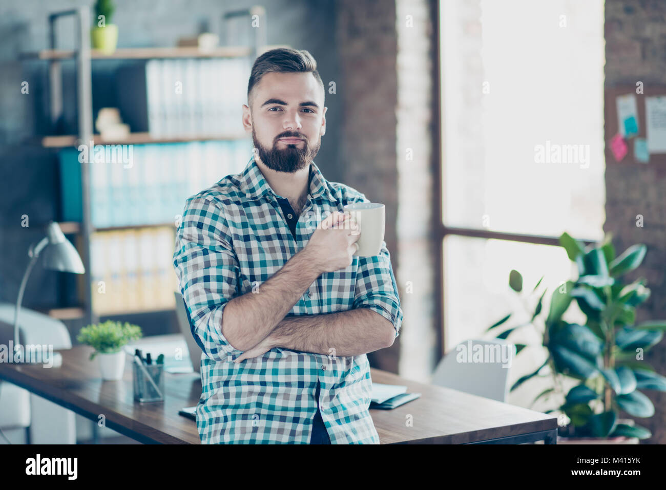 Coffee-time at work concept. Portrait of satisfied delightful confident employer drinking hot fresh aromatic latte - Stock Image