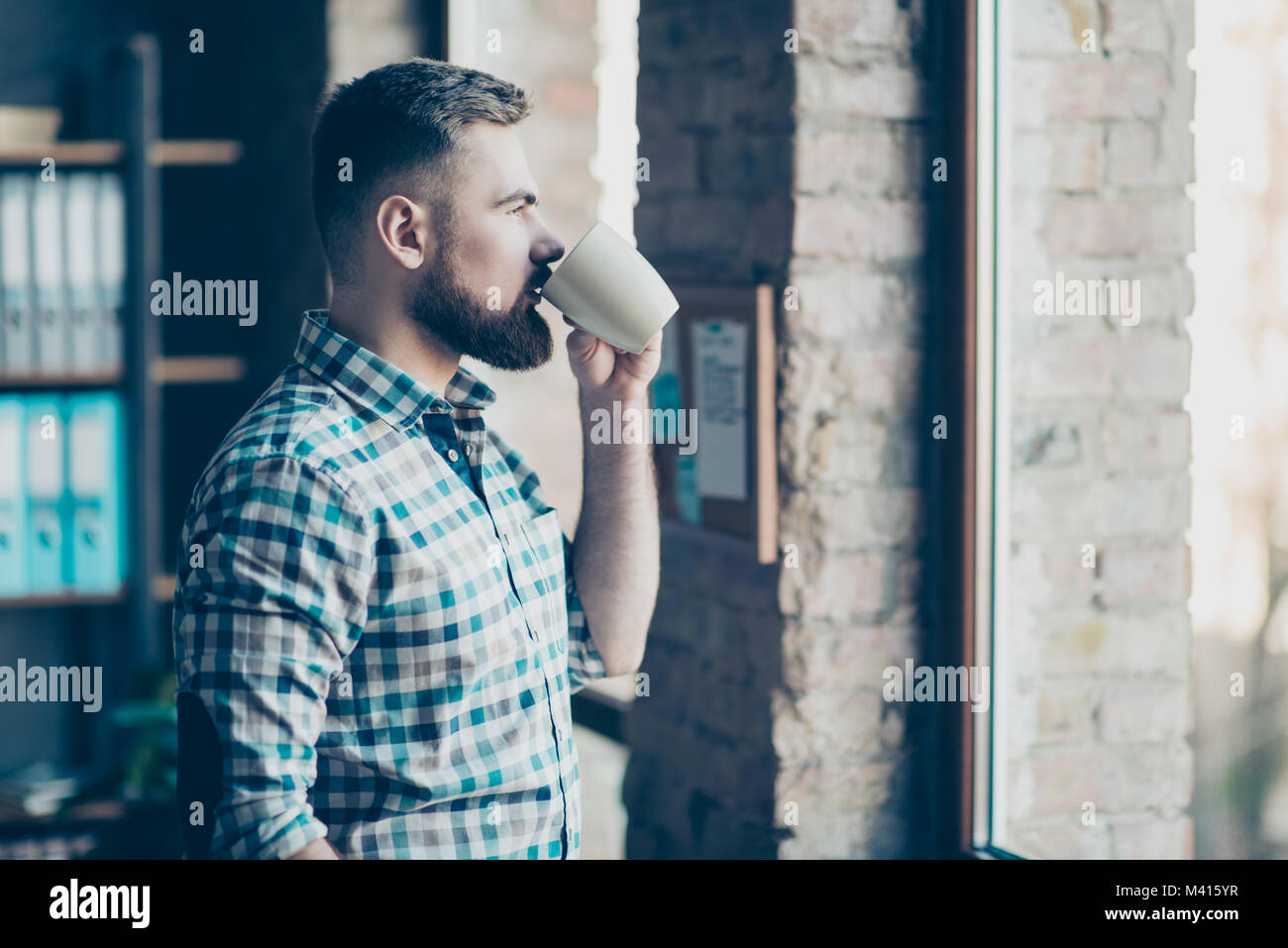Portrait of confident experienced calm peaceful concentrated bearded handsome guy having a recreating after hard - Stock Image