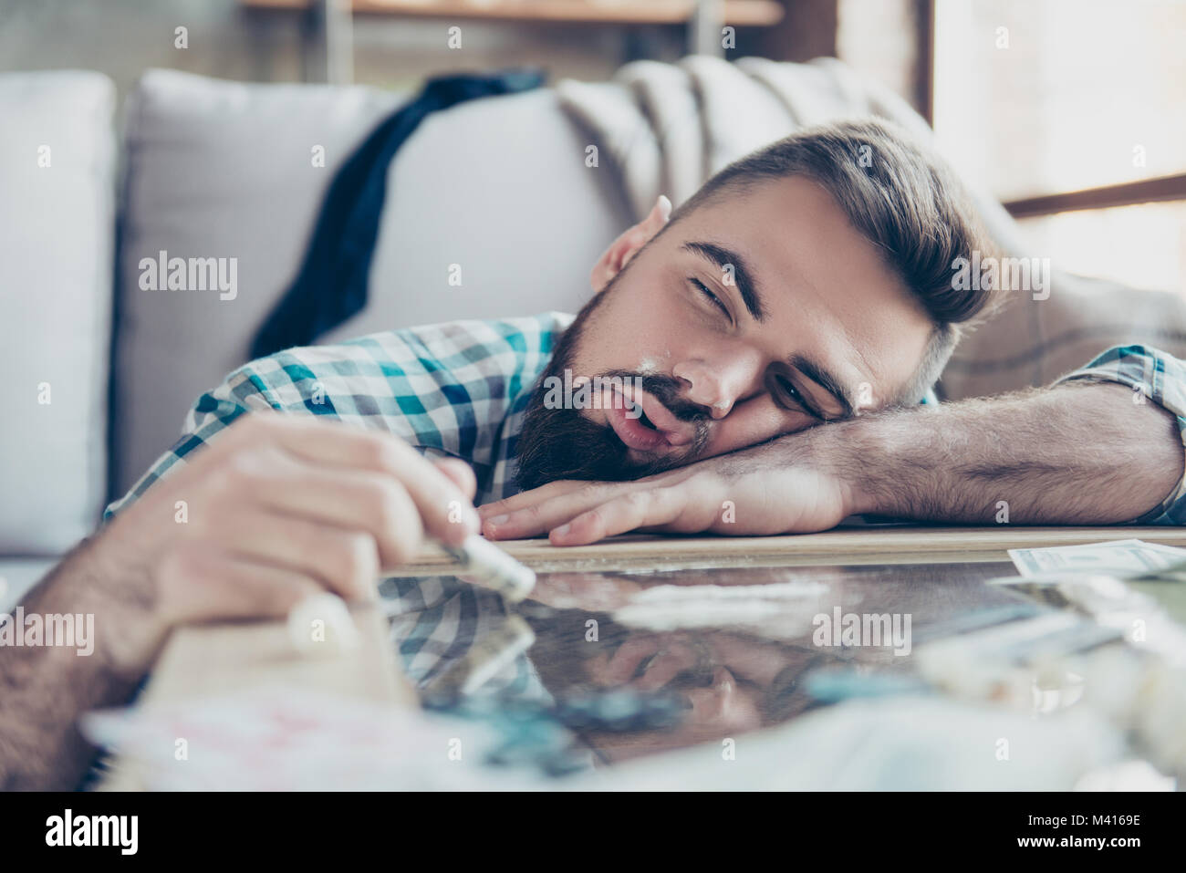 Close up photo of happy delightful feeling ecstasy bearded with stylish hairdo, he is lying on a table after sniffing - Stock Image