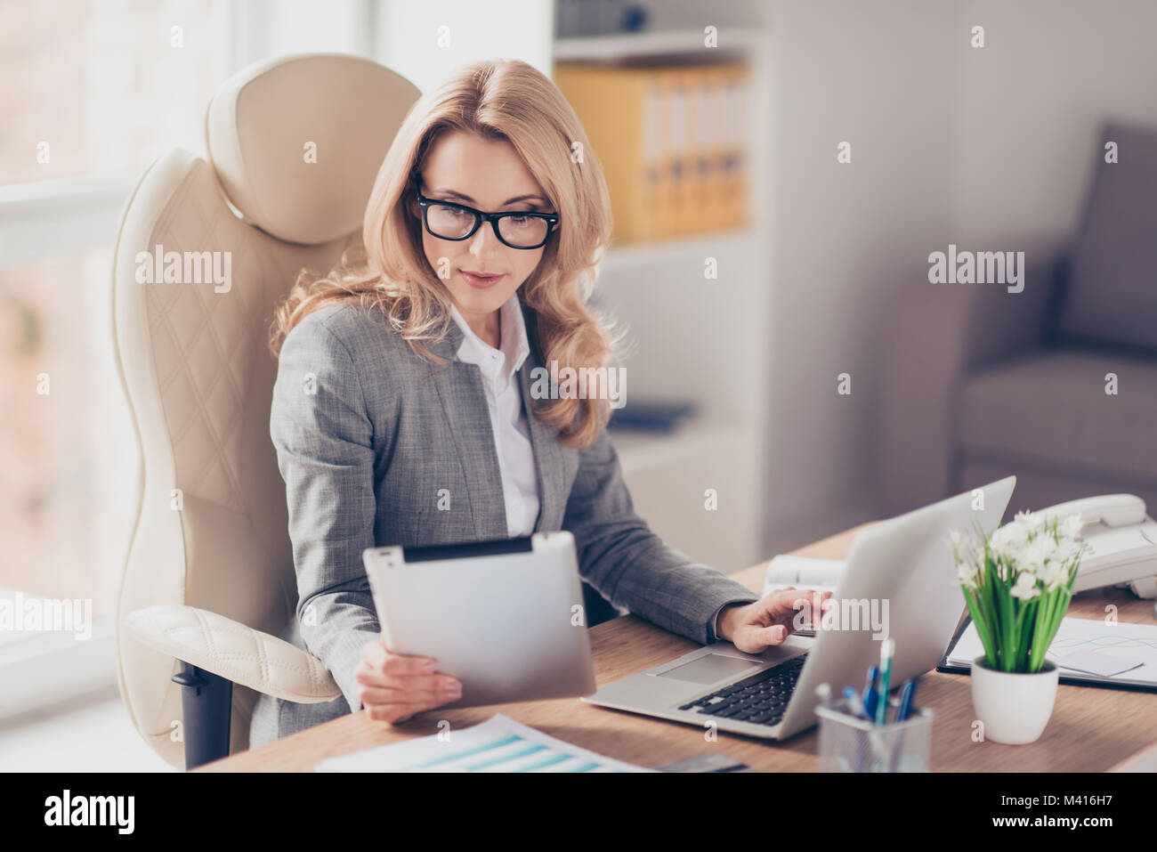 Pretty, charming, blonde woman using, browsing, typing, searching, expertising, working online on computer and tablet - Stock Image