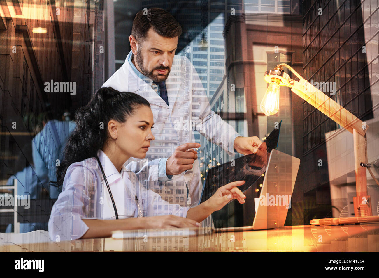 Serious doctors looking at the laptop while discussing an X ray plate - Stock Image