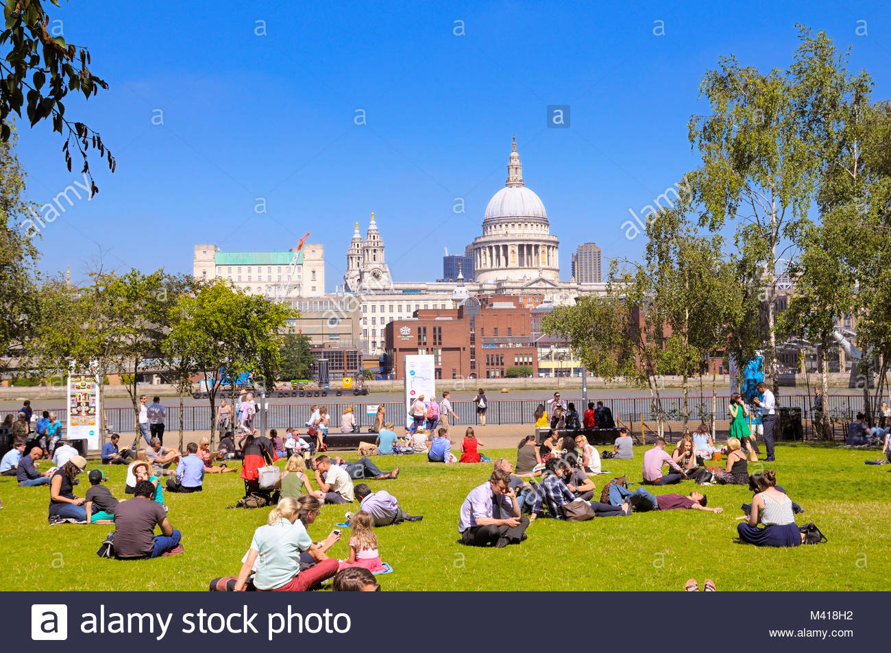 People relaxing in Tate Modern gardens opposite St Paul's Cathedral, London, England, UK Stock Photo