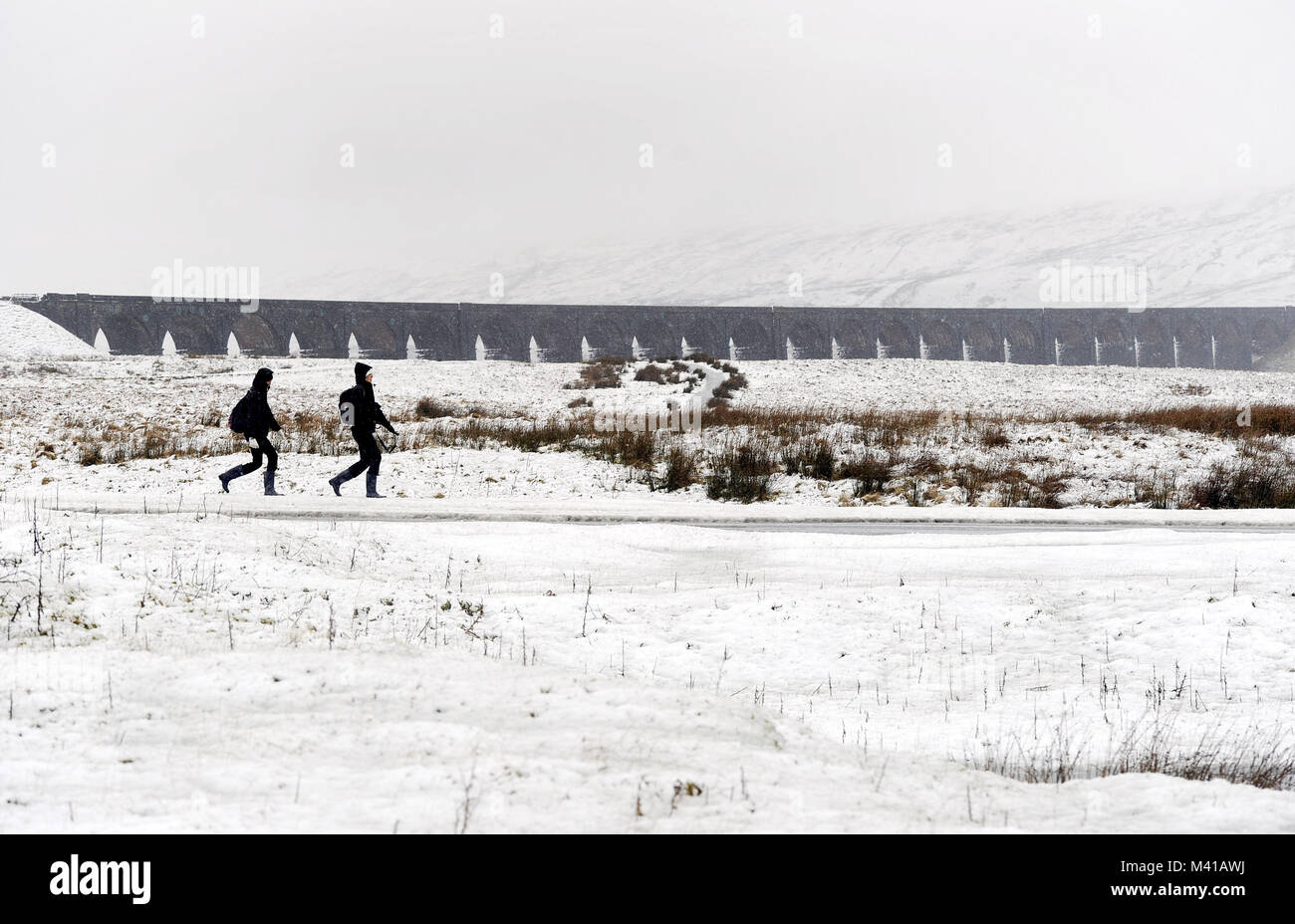 Walkers pass Ribblehead Viaduct in Yorkshire surrounded by heavy snow, as forecasters have issued a series of yellow - Stock Image