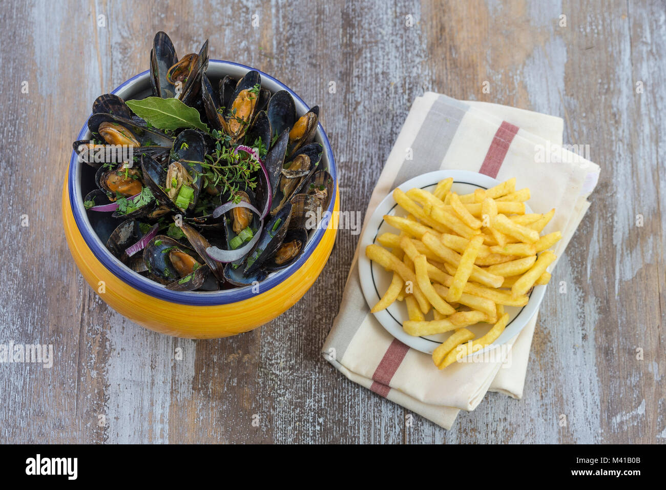 French blue mussel with herbs in a yellow bowl with french fries glass ramekin on napkin Seafood in a wooden board - Stock Image