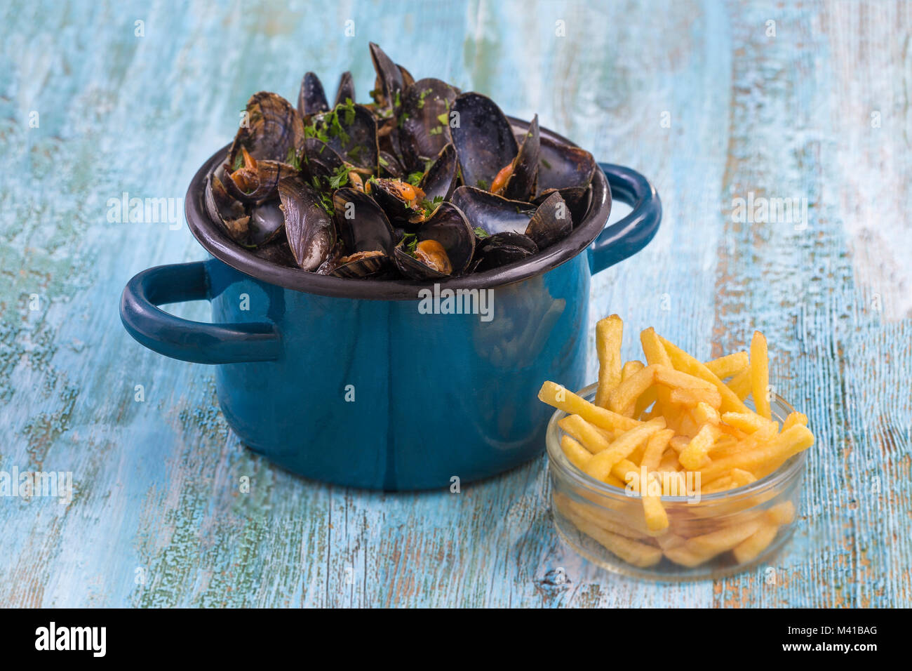 mussels in a blue ceramic pot on a blue wooden background. with a glass bowl of french fries. Brlgium lifestyle. - Stock Image