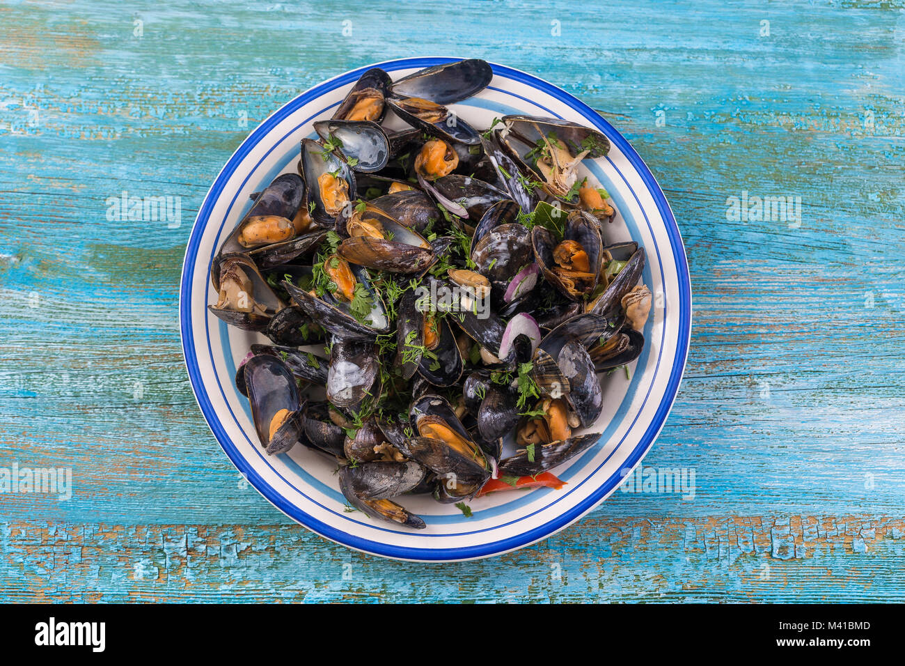 Steamed mussels in white wine with herbs ,Seafood. Served in white plate, up view on blue wooden background - Stock Image