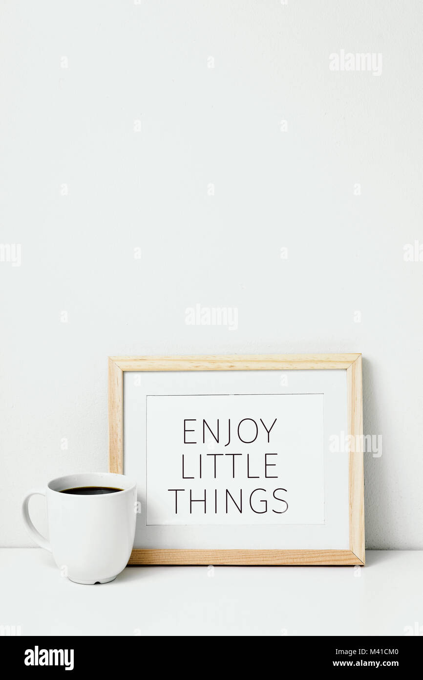 a wooden-framed picture with the text enjoy little things written in it and a cup of coffee, on a whit table against - Stock Image