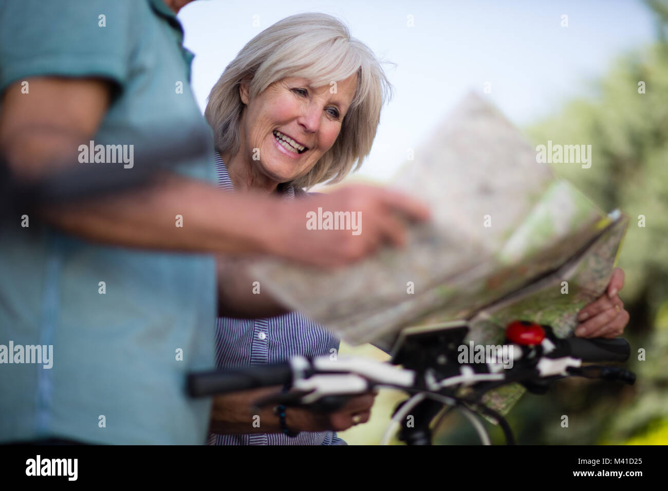 Senior couple looking at map on cycling vacation - Stock Image