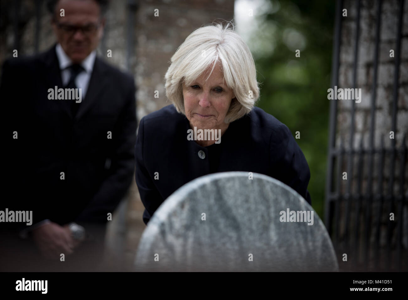 Senior woman reading a gravestone - Stock Image