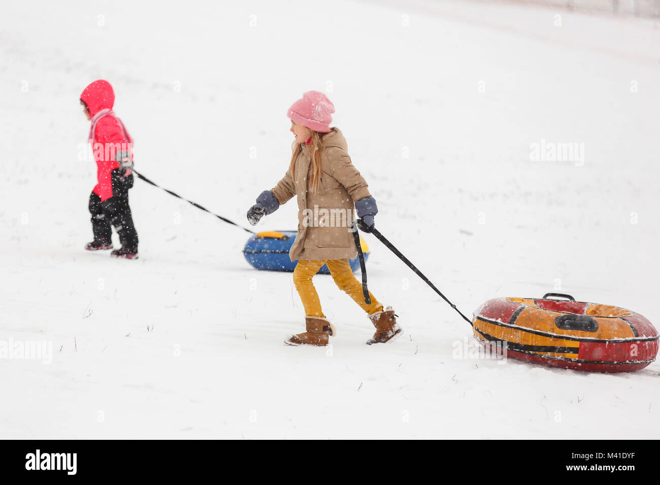 Photo of two girls on walk with tubing in winter park Stock Photo