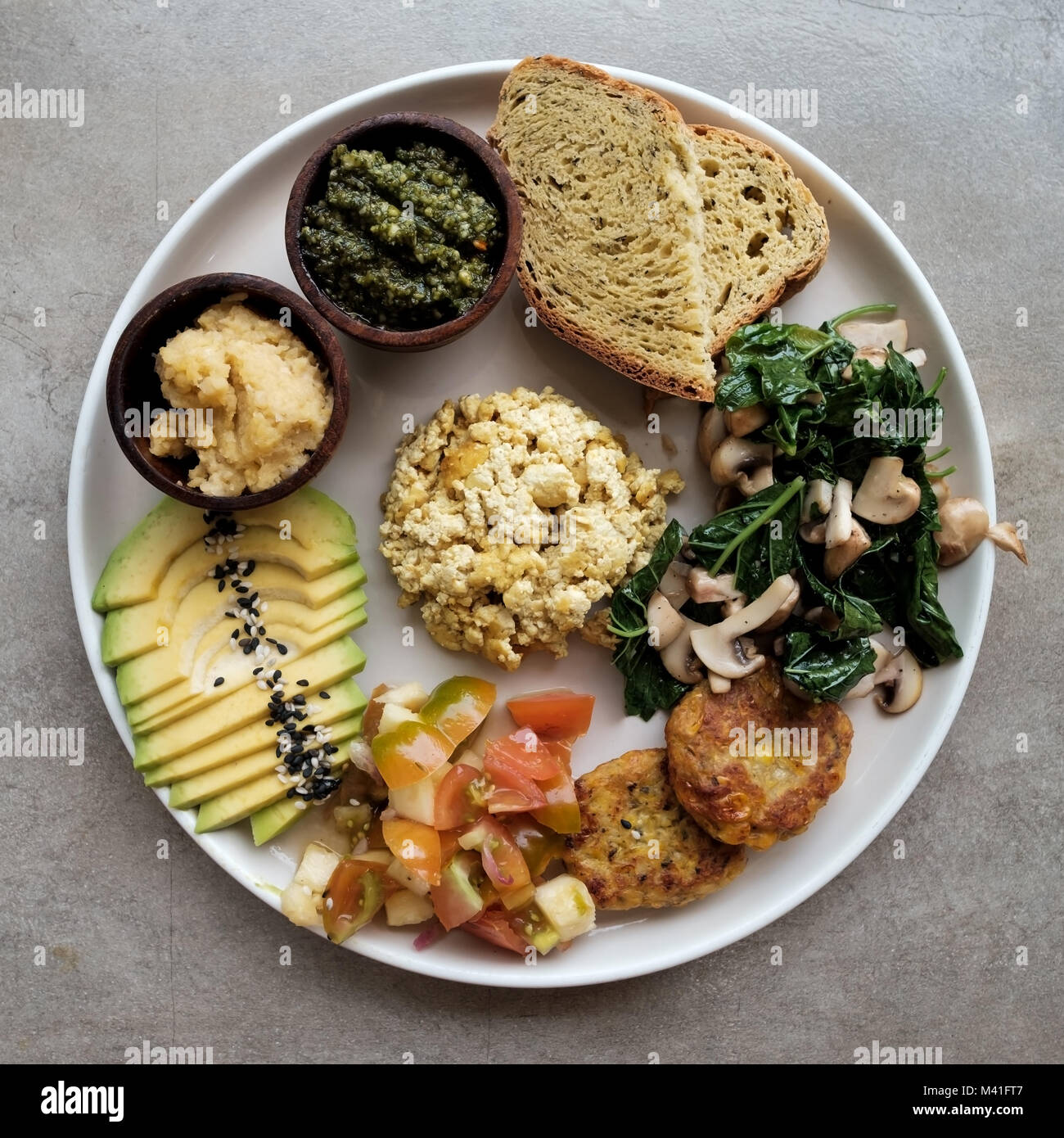 Vegan tofu with avocado, bread, vegetables and source close-up on a plate. - Stock Image