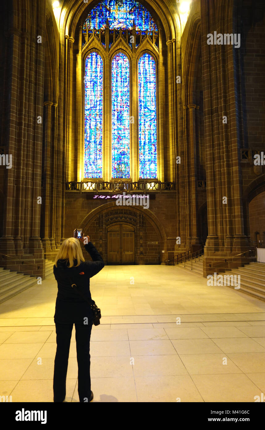 Woman Taking Photos of The Great West Window & the Tracey Emin's art work (I Feel You And I Know You Love Me) in Stock Photo