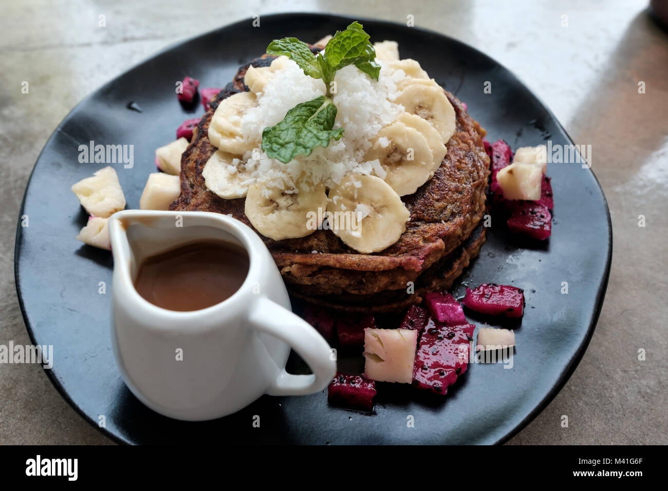 Vegan brown pancakes with banana and chocolate source for breakfast. - Stock Image