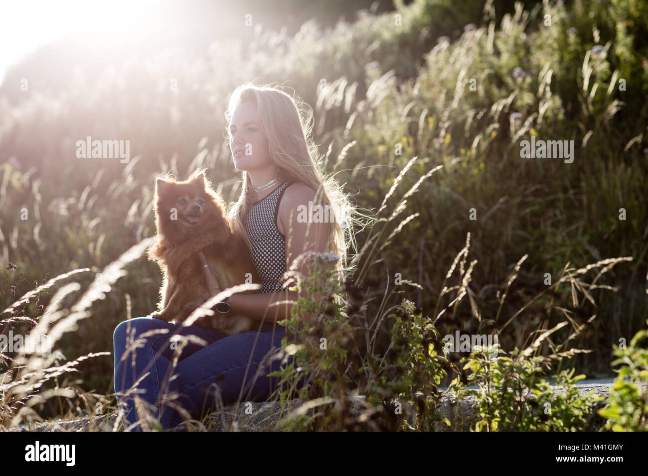Young Female cuddling her pet dog in countryside - Stock Image