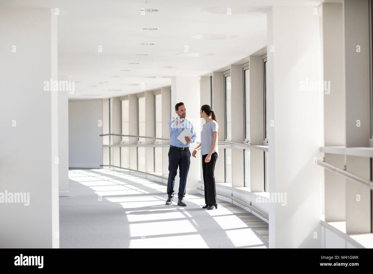 Businessman welcoming new employee to office - Stock Image