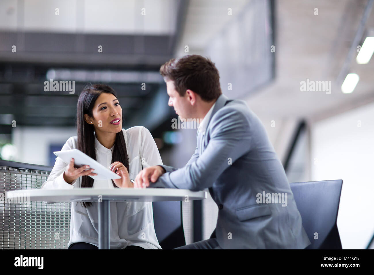 Colleagues in an informal business meeting using a digital tablet - Stock Image