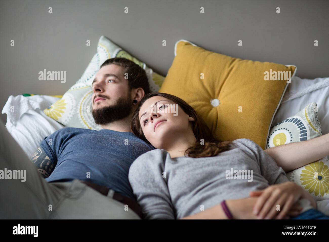 Young couple relaxing in bed - Stock Image