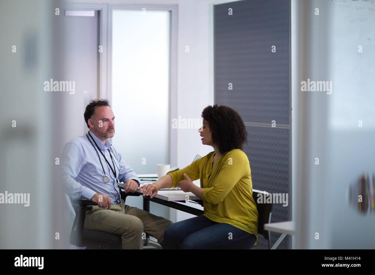 Male Medical Doctor listening to patient symptoms - Stock Image