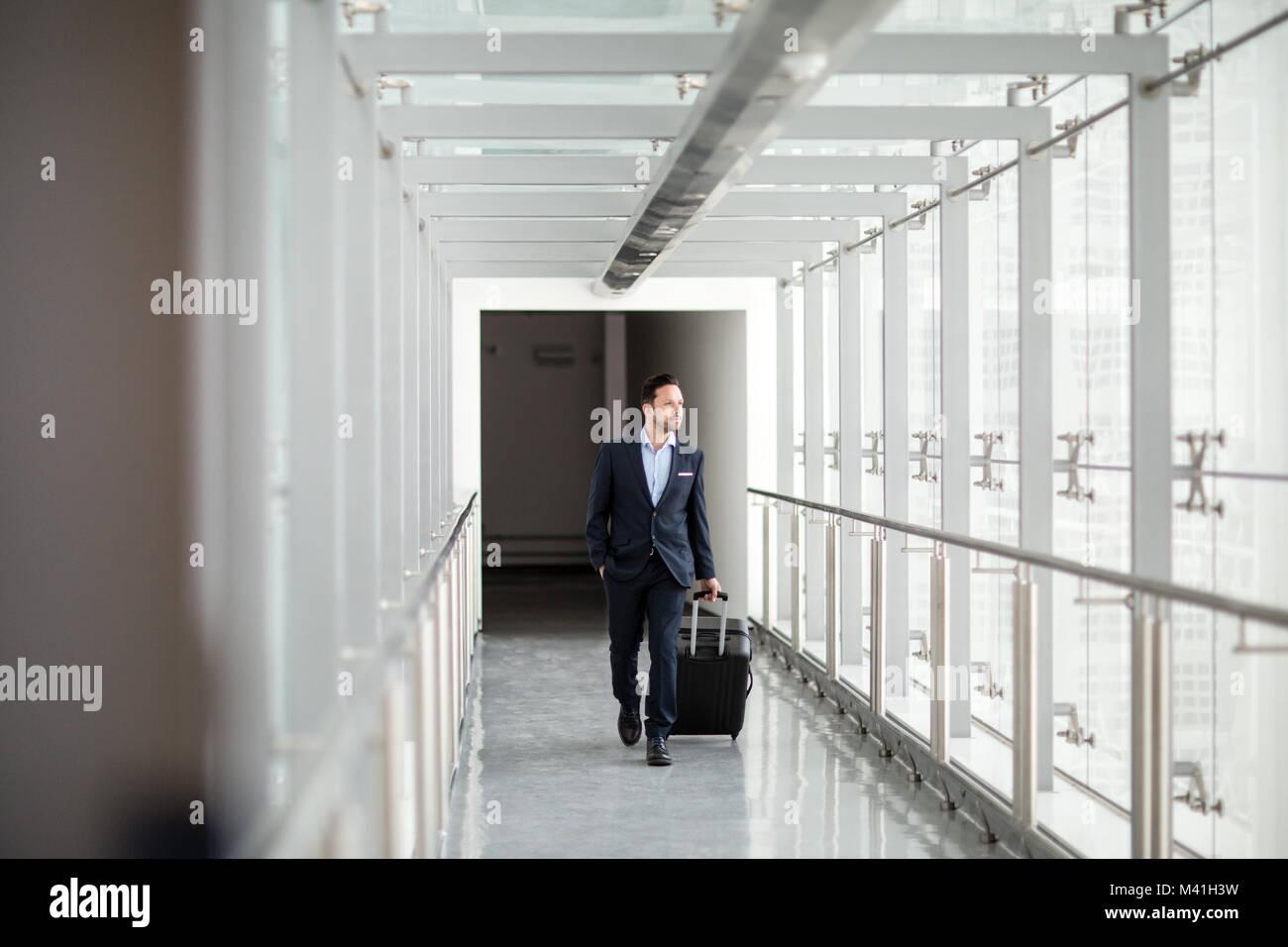 Businessman walking through airport terminal - Stock Image
