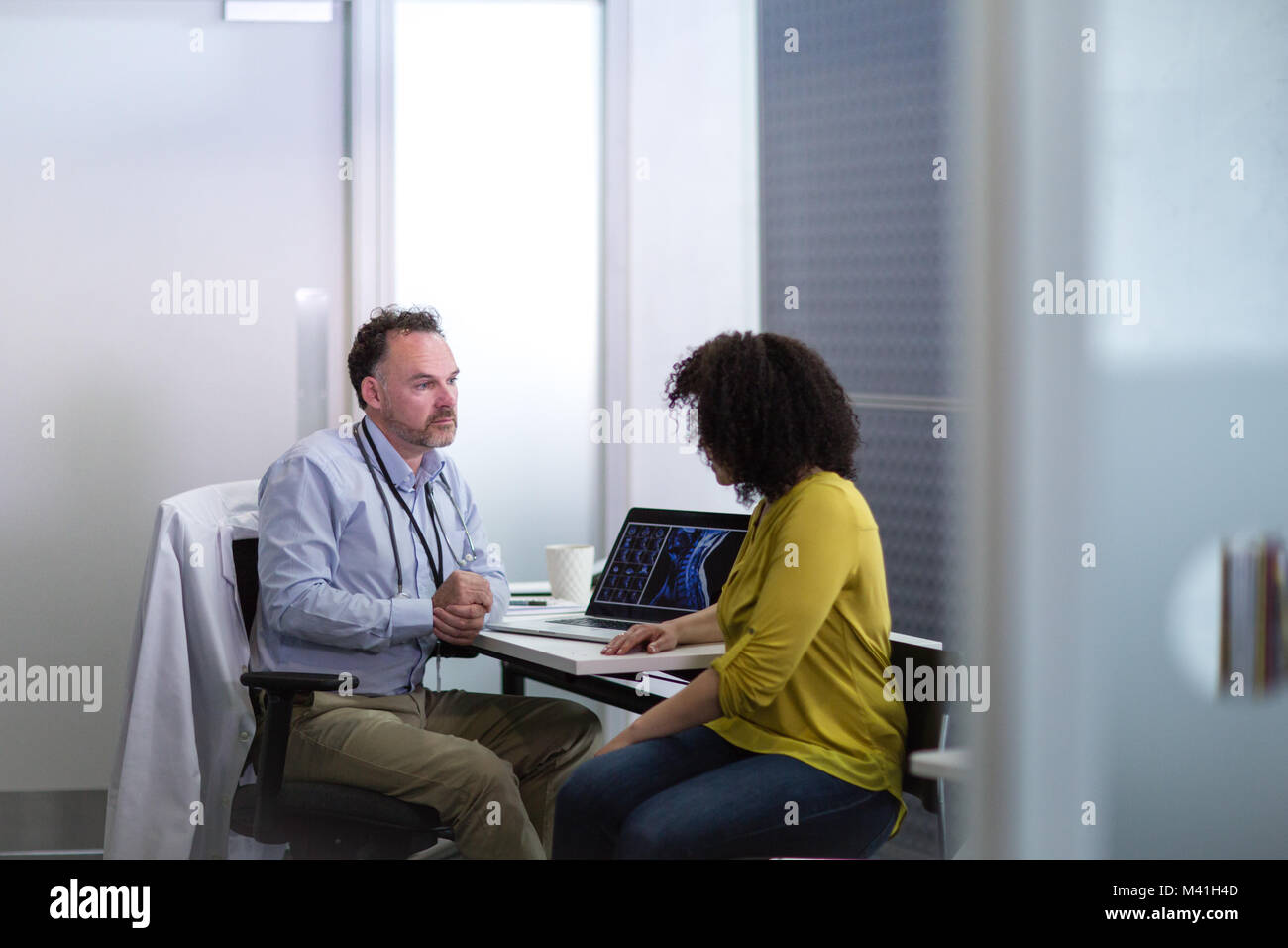 Male Medical Doctor explaining xray results to patient - Stock Image