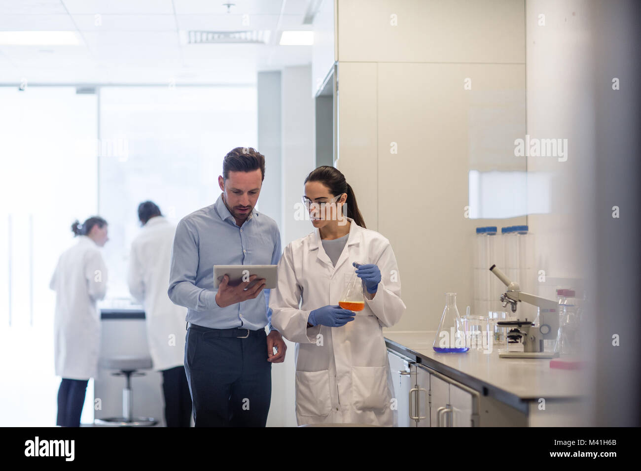 Female scientist discussing results of experiment with male colleague - Stock Image