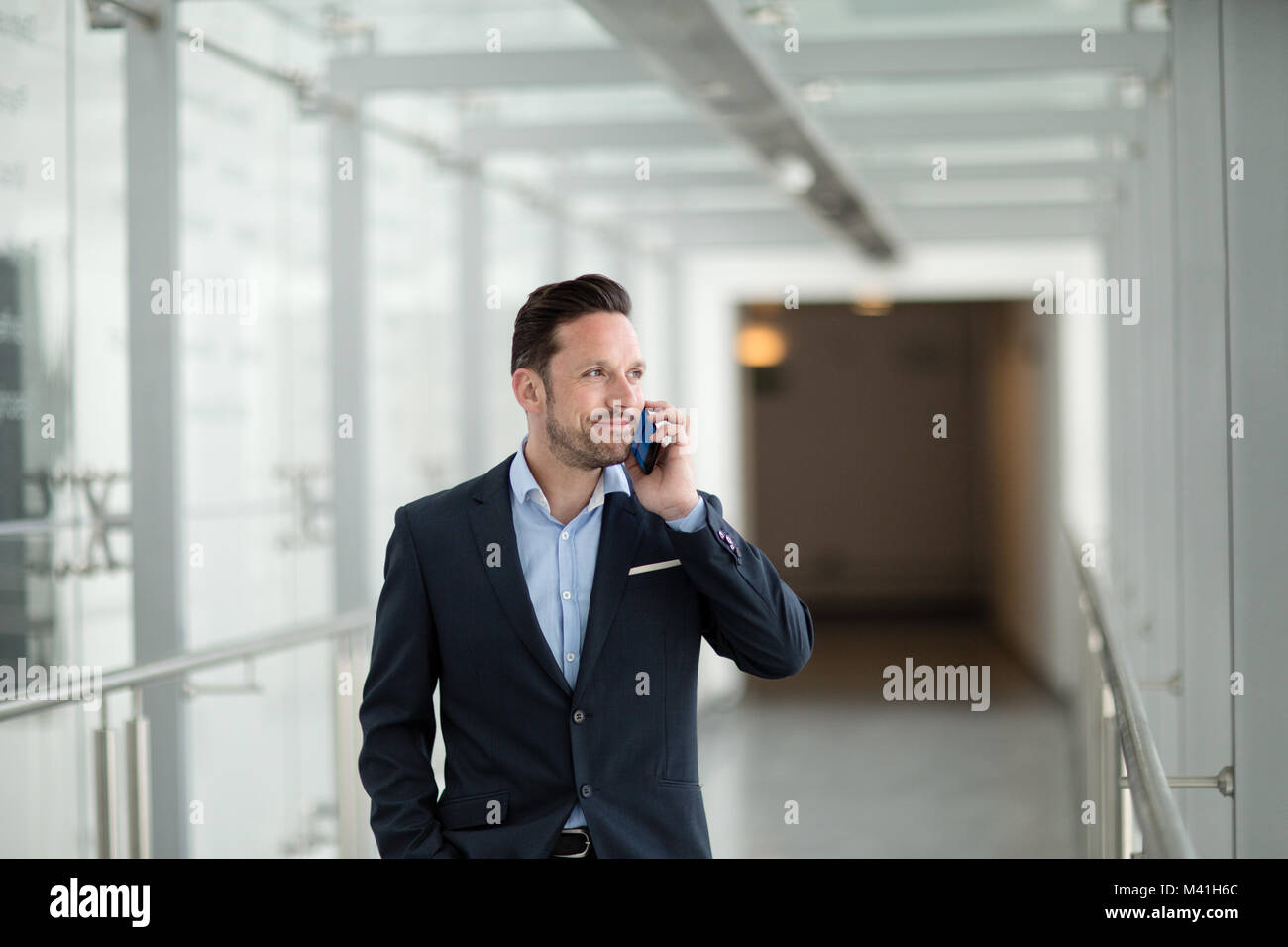 Businessman using smartphone on his commute - Stock Image