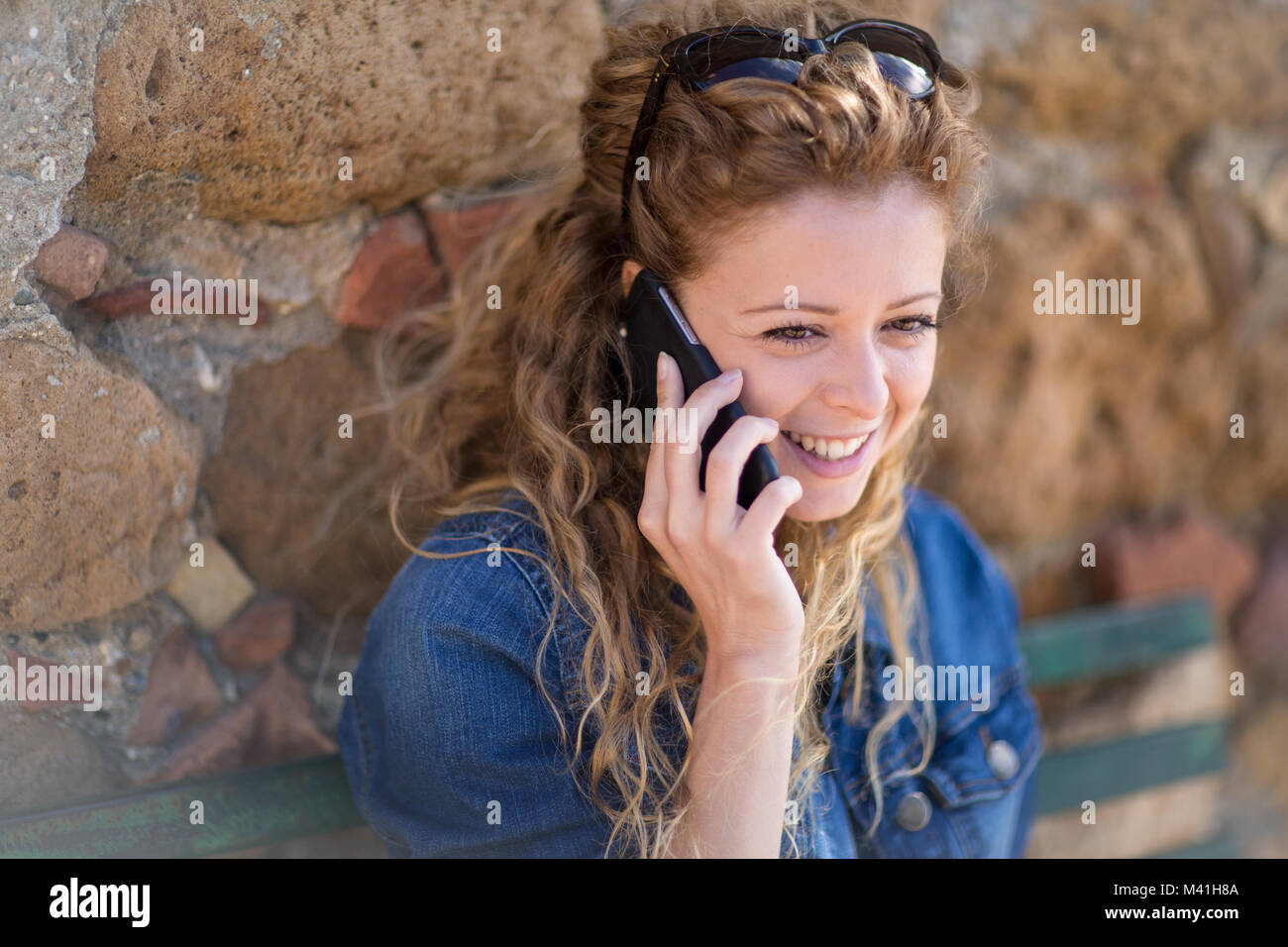 Young adult female talking on phone - Stock Image