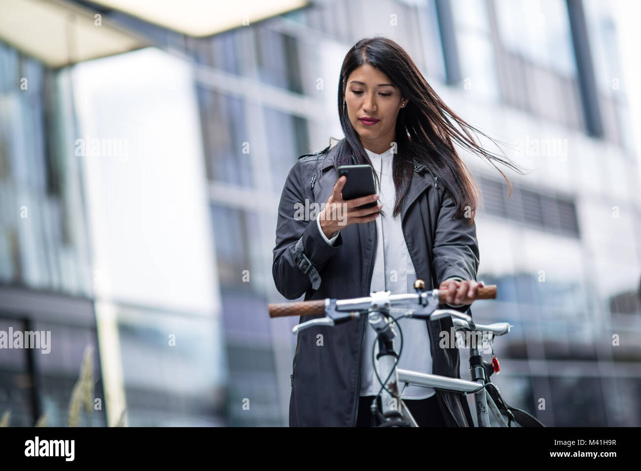 Businesswoman cycling to work using smartphone - Stock Image