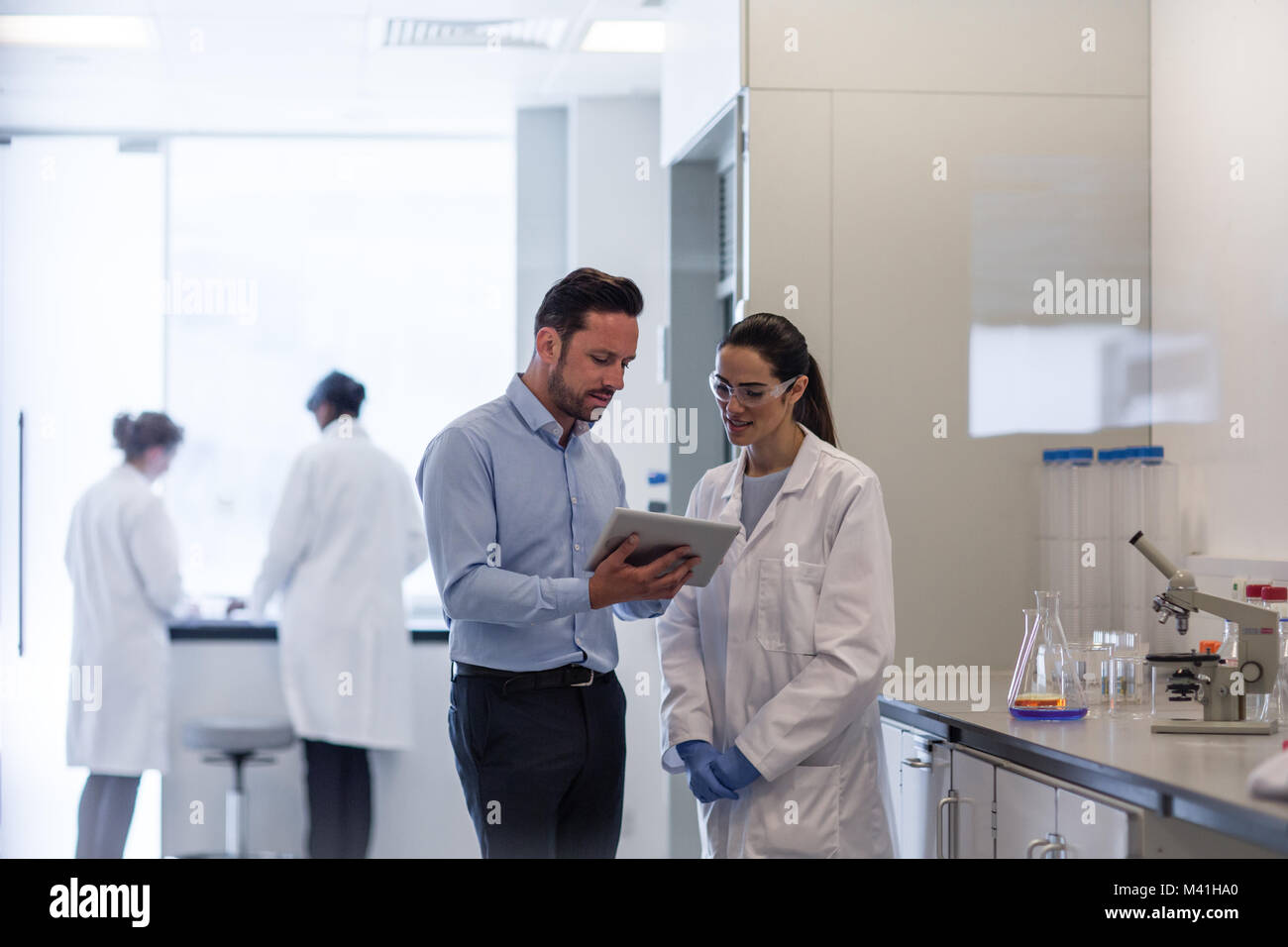Female Scientist Discussing Data With Pharmaceutical Sales Rep   Stock Image