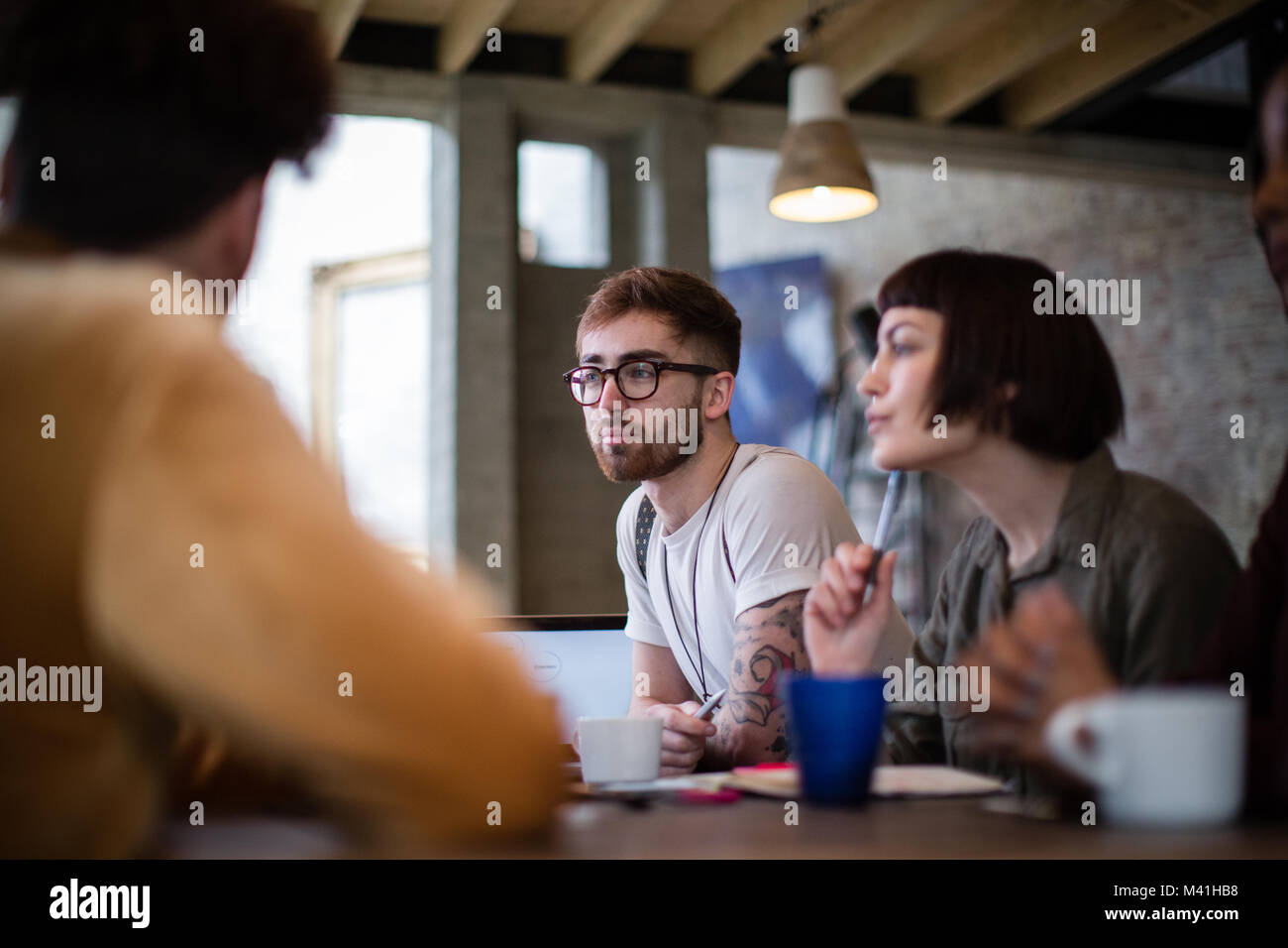 Group of young entrepreneurs listening to a presentation - Stock Image