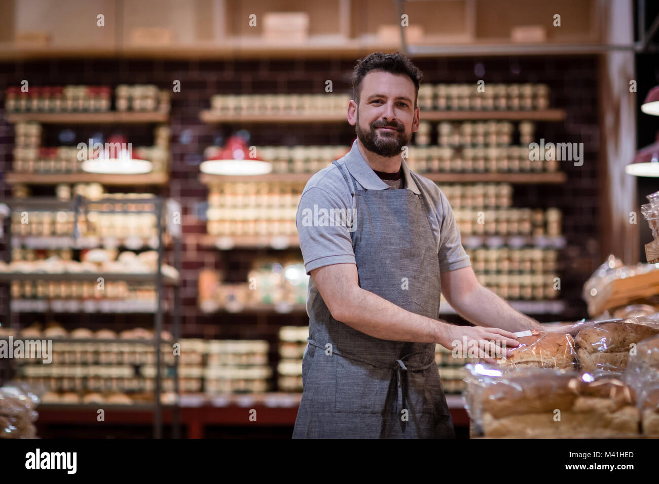 Baker in bakery looking to camera - Stock Image