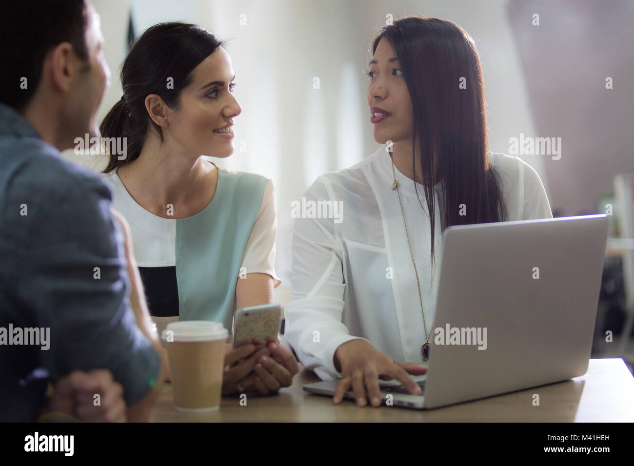 Colleagues in café looking at laptop - Stock Image