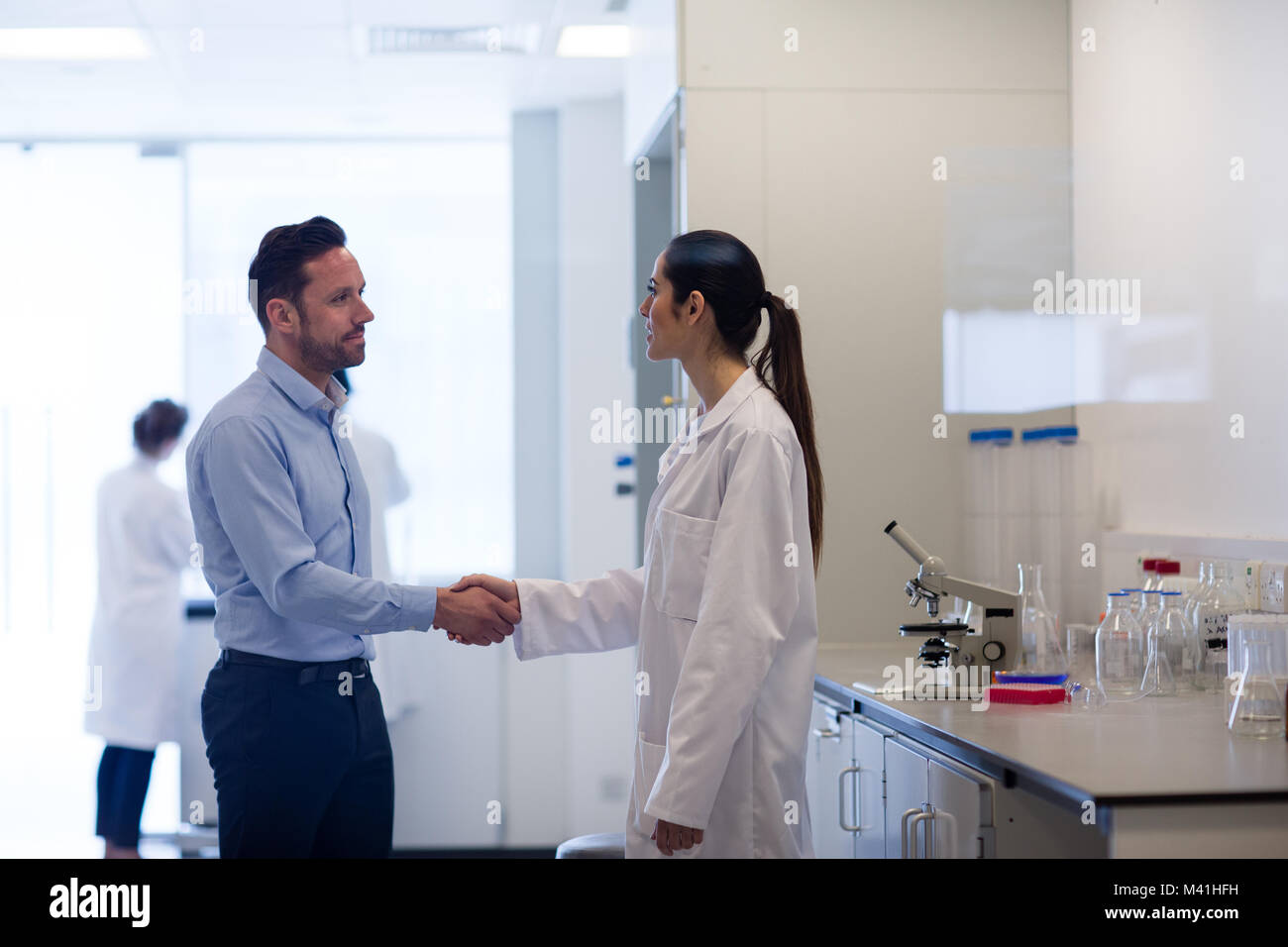 Female Scientist Shaking Hands With Pharmaceutical Sales Rep   Stock Image