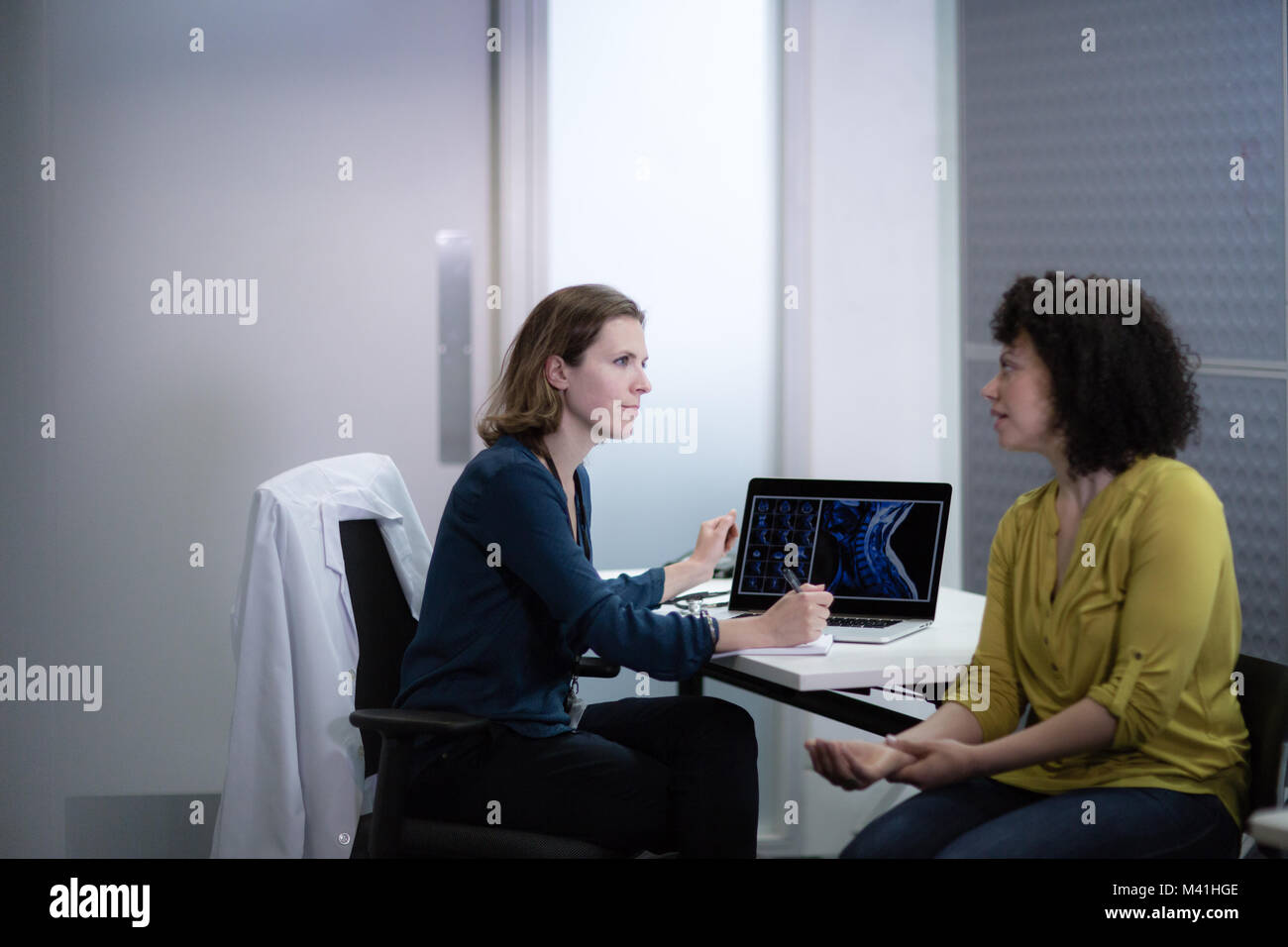 Female Medical Doctor listening to patient symptoms - Stock Image