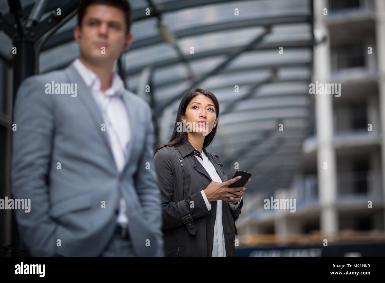 Businesswoman waiting for train on platform with smartphone in hand - Stock Image